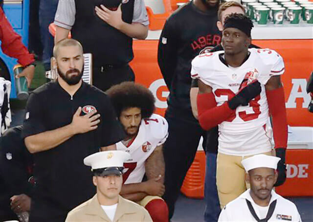 San Francisco 49ers quarterback Colin Kaepernick, middle, kneels during the national anthem before the team's NFL preseason football game against the San Diego Chargers, Sept. 1 in San Diego. Multimedia Accuplacer/AP