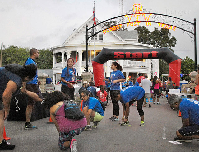 Students at this college stretch before an early morning race at the Mascarita Run 5K Oct. 15 on 10th Street. Marisa Martinez, senior specialist for student success, organized participation in the race for students who like to participate in running events.  Photo by Deandra Gonzalez