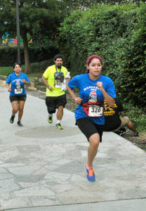 Math freshman Ingrid Zamora sprints to the finish line to complete her run at the Mascarita Run 5K Oct. 15 downtown. Zamora attended the run with 314 other people who signed up and were awarded for their times in different age groups.  Photo by Deandra Gonzalez
