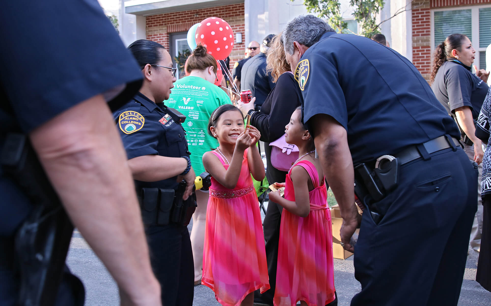 Faith and Hope Calma, daughters of Alamo Colleges officer Merasol Malapo, left, admire a badge sticker with Deputy Chief Joe Curiel Oct. 6, 2015, during this college's first National Night Out hosted by the Alamo Colleges' police department on West Evergreen and North Main Ave. About 250 people partook in free soda, water, burgers and sausage wraps provided by Luther's Cafe and Alamo Colleges officers. File