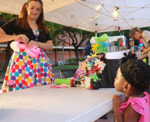 "Madison Lundy, 3, watches balloon artist Holly ""Twister Sister"" George make a Cinderella balloon for Lundy. The fourth SACtacular took place Oct. 14 west of the nursing complex building to west side of chemistry and geology. Clubs and organizations either were giving information or selling food and drinks. Photo by Aly Miranda"