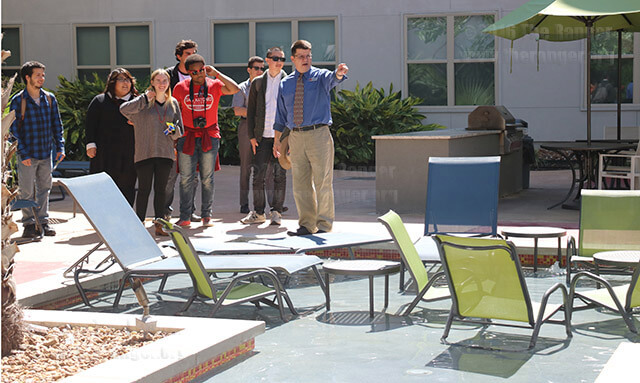 Tobin Lofts leasing manager Kevin Marshburn shows members of the Student Government Association the outdoor resort-style pool and lounging deck for residents during a tour of the Tobin Lofts Oct. 10. Other community amenities include a game room, fitness center and an outdoor barbecue station.  Photo by Alison Graef