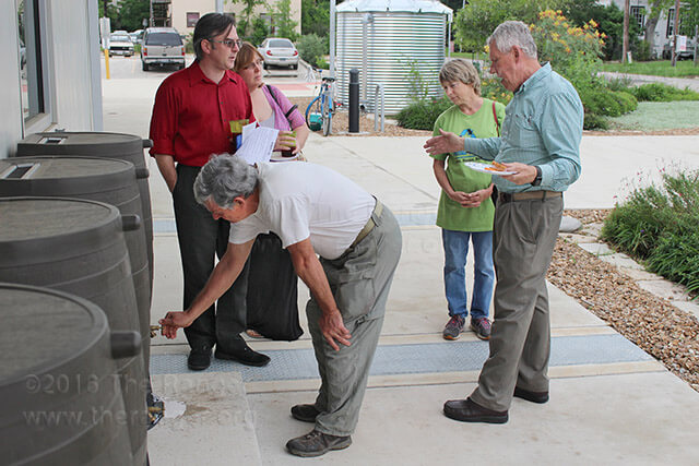 Steven Lewis, former continuing education program director, explains EcoCentro's rain water collection process April 22, 2015. Five smaller barrels hold 200 gallons each and are available for residential use. The larger well holds 2,700 gallons.
