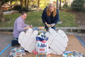 "Fine arts chair Jeff Hunt and Dr. Teanna Staggs, chemistry and geology chair, put together canned goods and boxes to make up a symbolic ""helping hand"" for the ""SAC spirit"" category in the food drive and sculpture contest Nov. 15 in the mall.  Photo by Aly Miranda"