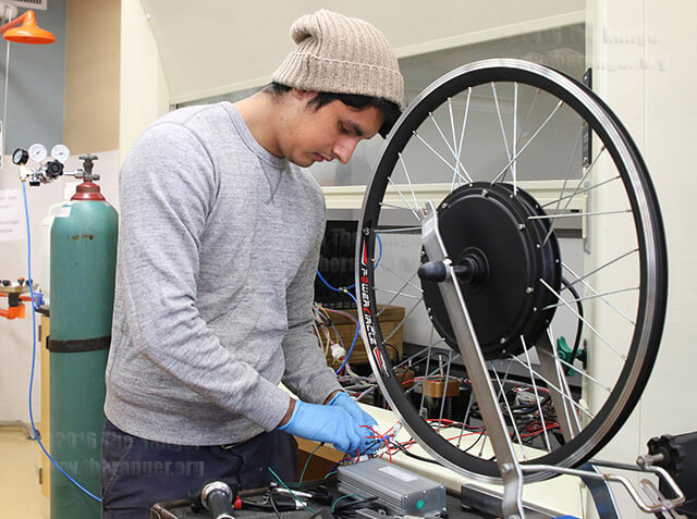Dominic Ochoa, engineering sophomore and project manager of SAC Motorsport, fixes the wires to the battery operating the hub-motor wheel for the hydrogen fuel-cell that will power a race car competing for the Shell Eco Marathon Completion of the Americas April 2017 in Detroit. Photo by Brianna Rodrigue