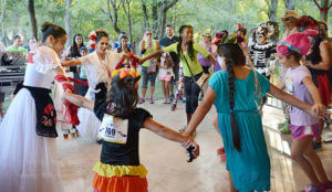 Folklorico dancers Mia Rodriguez and Cynthia Cabral dance with young participants before awards were given out at the Dia De Los Muertos 5K and 10K run Oct. 29 at Lady Bird Johnson Community Park. Photo by Deandra Gonzalez