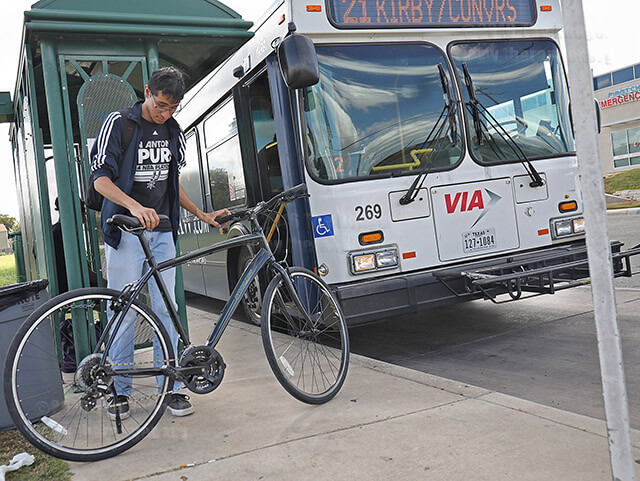 Journalism freshman Robert Aguinaga gets ready to board VIA bus Route 21 after traveling 1.7 miles by bike from Northeast Lakeview to Converse. Aguinaga lives near Sea World and rides two hours to get to Northeast Lakeview. Photo by Josue Hernandez