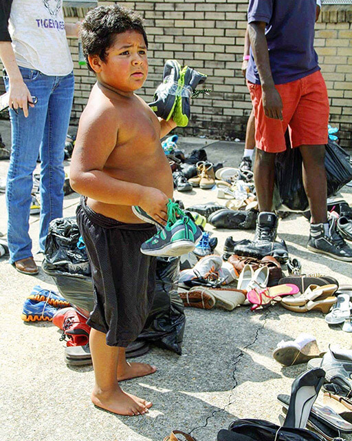 Matthew Gomez, 11, walks barefoot and shirtless through all the shoes that Castillo brought to New Iberia trying to decide which pair he wants. Courtesy